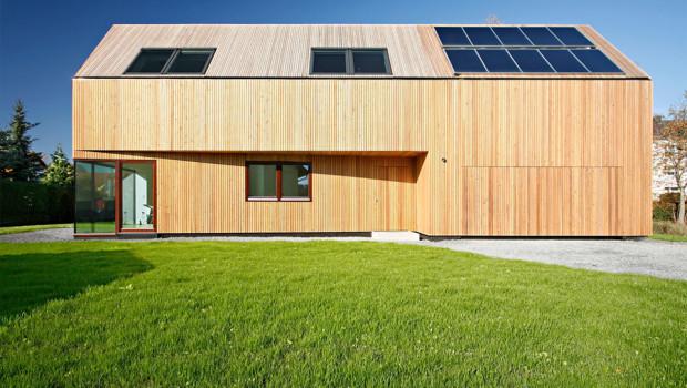 Aussenansicht des Niedrigenergiehauses mit Lärchenholzverkleidung der Fassade und Sonnenkollektoren auf dem Dach.