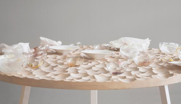 Großer UMAMI Tisch mit wellenförmigen Einkerbungen und leeren Glasschälchen.