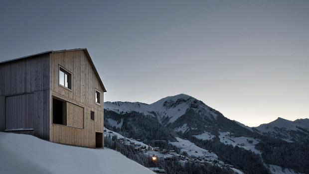 Holzhaus auf einem Plateau bei Dämmerung. Im Vordergrund eine Straße, im Hintergrund von Schnee bedeckte Berge.