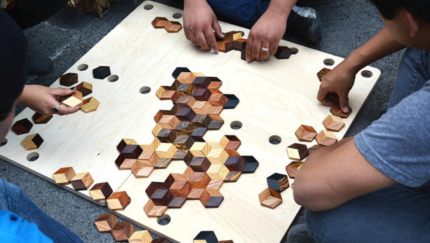 Vier Personen spielen das grid game auf dem Boden. Die Spielsteine befinden sich auf einem Holzbrett.