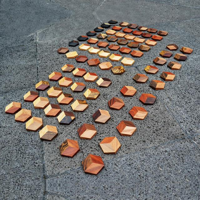 hölzerne, hexagonale Spielsteine aufgereiht auf Steinboden. Das Holz leuchtet golden.
