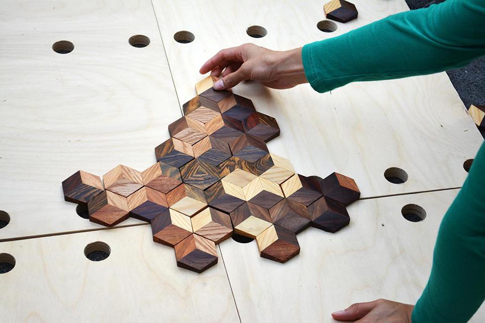 Das grid game wird auf dem Boden gespielt. Eine Person stützt sich auf und legt einen Spielstein.