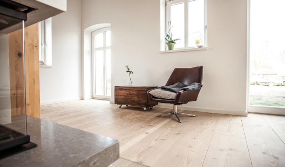 Das Bild zeigt eine Zimmerecke des Wohn-und Essbereichs. Ein dunkler Ledersessel und eine alte Holztruhe sind zu sehen. Sie stehen auf breiten Douglasie Dielen.