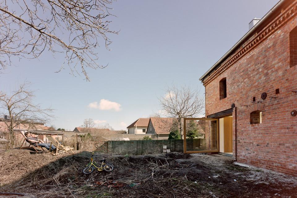 Auf der rechten Seite des Bildes der Ausschnitt eines Backsteinhauses. Eine große verglaste Tür öffnet sich nach draussen in den Vorgarten. Der unfertige Vorgarten besteht aus Ästen und aufgehäufter Erde. Am linken Rand zwei Liegestühle. Ein Mann lässt sich darin sonnen.
