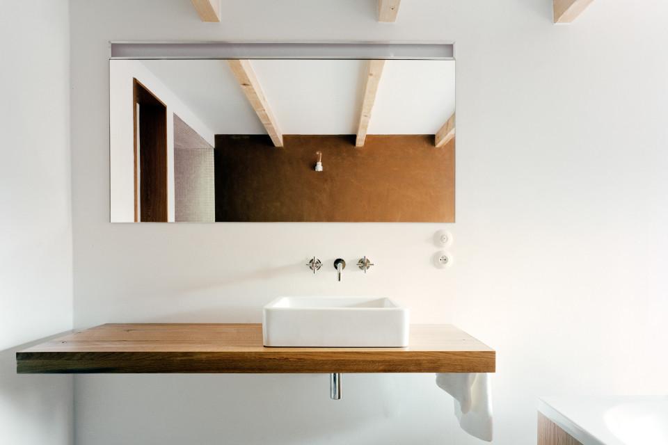 Man blickt frontal auf die Badezimmer Armatur, welche auf einer Holzdiele montiert wurde. Der hintere Teil des Zimmers spiegelt sich in einem großen Badezimmerspiegel wider.