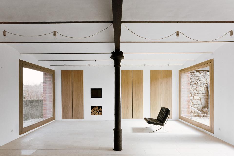 Man blickt in einen offenen Raum, mit großen Fenstern. An den Wänden sind große Holzdielen zu sehen. Es befindet sich nur ein schwarzes, kleines Sofa im Raum, ansonsten steht er leer.