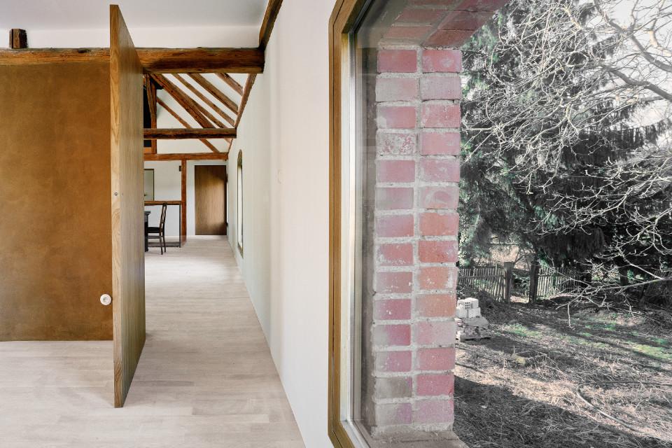 Das Bild teilt sich visuell in zwei Hälften. Auf der linken Seite blickt man in ein Haus mit Holzboden und alten Dachbalken. Auf der rechten Seite des Bildes blickt man hinaus aus einem großen Fenster und hinein in einen Garten.