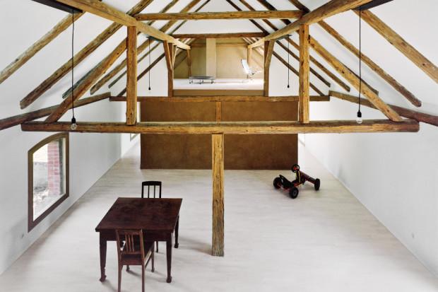 Man blickt in einen offenen Wohnraum in einem alten, renovierten Bauernhof. Die hölzernen Dachbalken sind sichtbar.