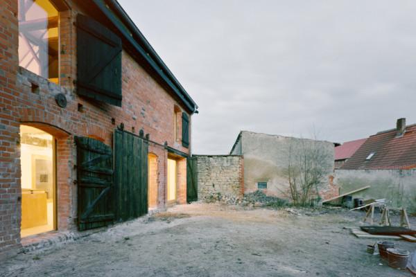 Das Bild zeigt ein altes Gebäude aus roten Backsteinen. Die rechten zwei Drittel des Bildes zeigen einen heruntergekommenen Vorgarten. Der Himmel ist bewölkt und grau. Vom Innern des Hauses scheint warmes Licht nach draussen.