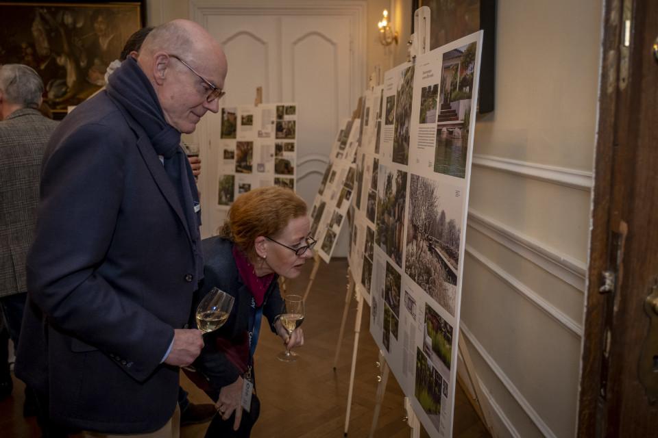 Man sieht zwei Besucher der Preisverleihung. Sie schauen sich die Projekte auf einem Aussteller an.