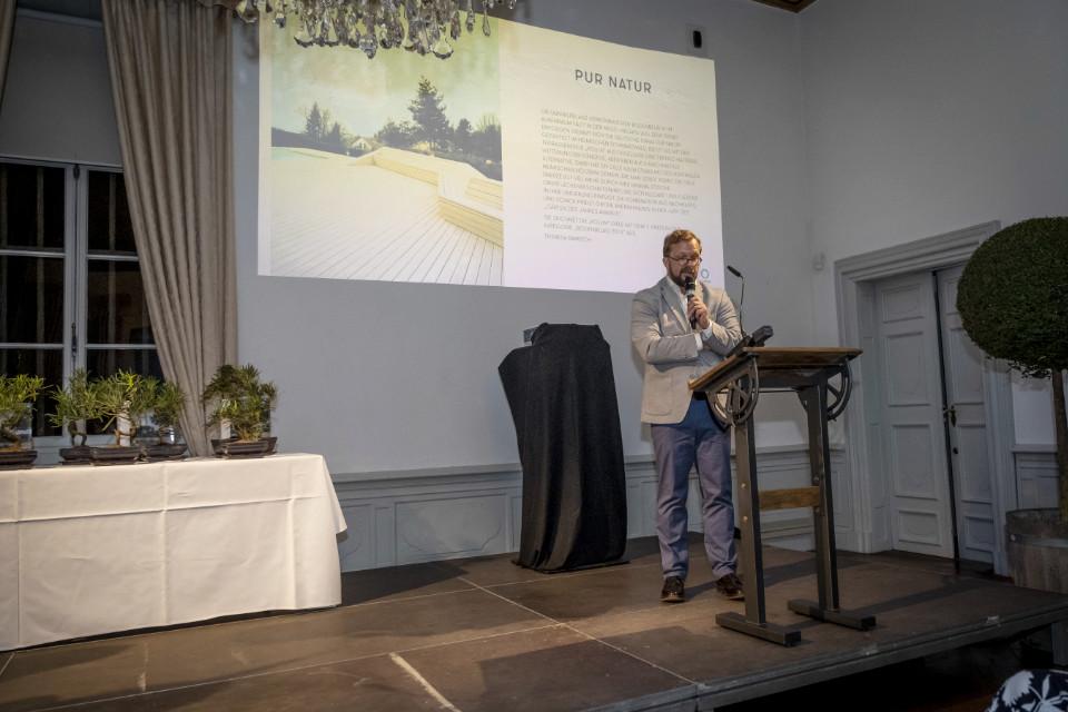 Andreas Hagenkord steht am Podest und spricht in ein Mikrofon. Im Hintergrund sieht man das Bild einer Terrasse aus Kollin Dielen. Das Bild und ein Text der der Jury sind an die Wand projekziert.